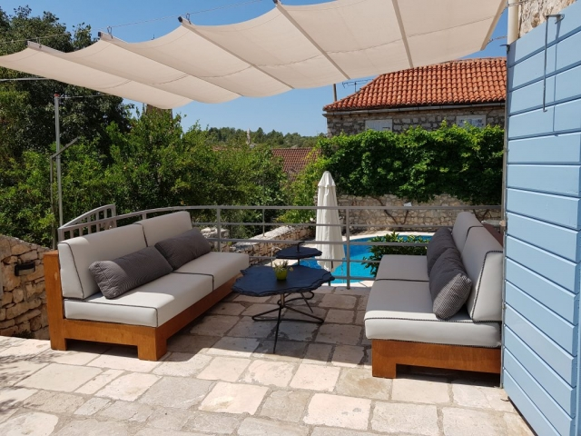Shaded garden furniture overlooking the swimming pool