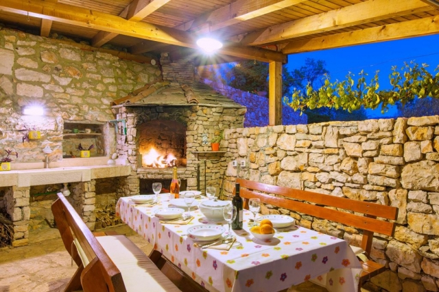 Outdoor covered dining area with open fireplace